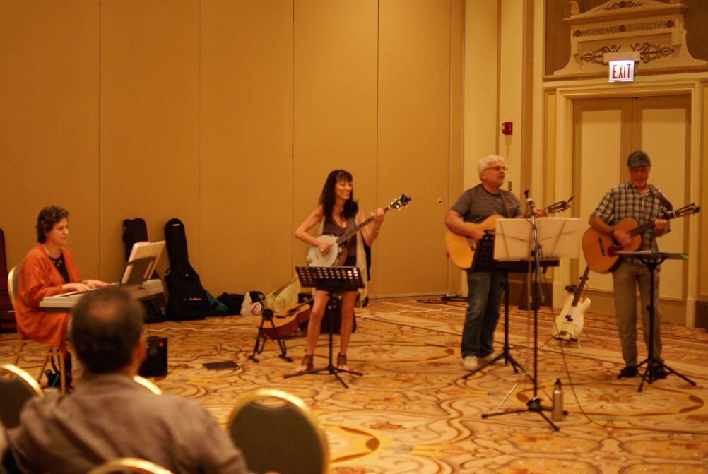 On the left, Esther plays keyboard, and Mary Gault, Larry Hazard and Bill Lange strum their strings.