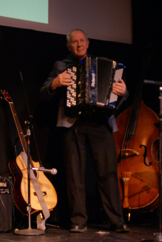 Multi-instrumentalist  Michael Lieber stands between his bass guitar and his upright bass and plays his accordion.