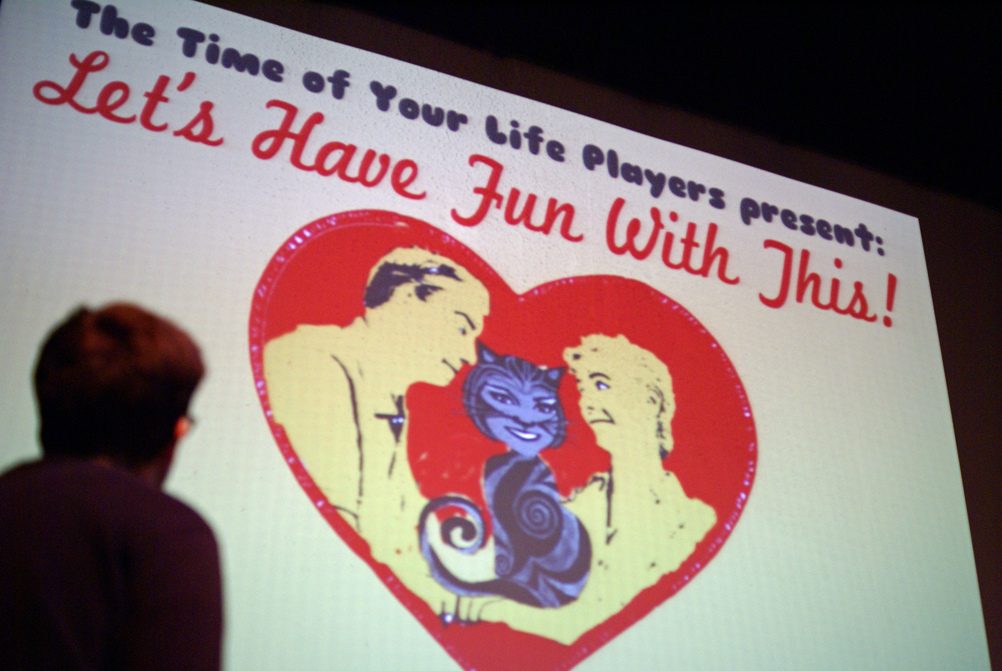 "Mike Evans, Musical Director, looks up at the ""Let's Have Fun With This"" logo projected on the big screen."