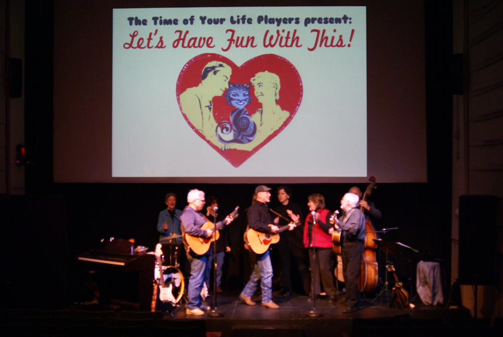 "Time of Your Life Players perform onstage at the Wilmette Theatre, with the ""Let's Have Fun With This"" logo projected above them. From left to right: Judith Muench; Larry Hazard; Tery Veras; Bill Lange, Guitar; Ester Lieber; Annie Kontak; Steve Bishop; and Michael Lieber, Bass."