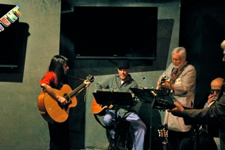 Bill Lange. Seated in the center, Bill Lange plays guitar with Mary Gault and Steve Bishop.